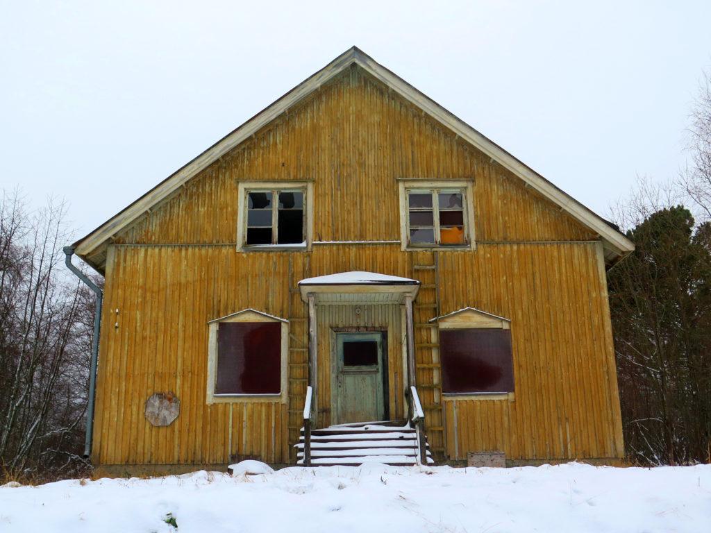 Hylätty Rytikarin opettajien asuntola. Ikkunat on peitetty ja rikottu, maalit kuluneet, itse talo näyttää ihmeen suoraryhtiseltä.