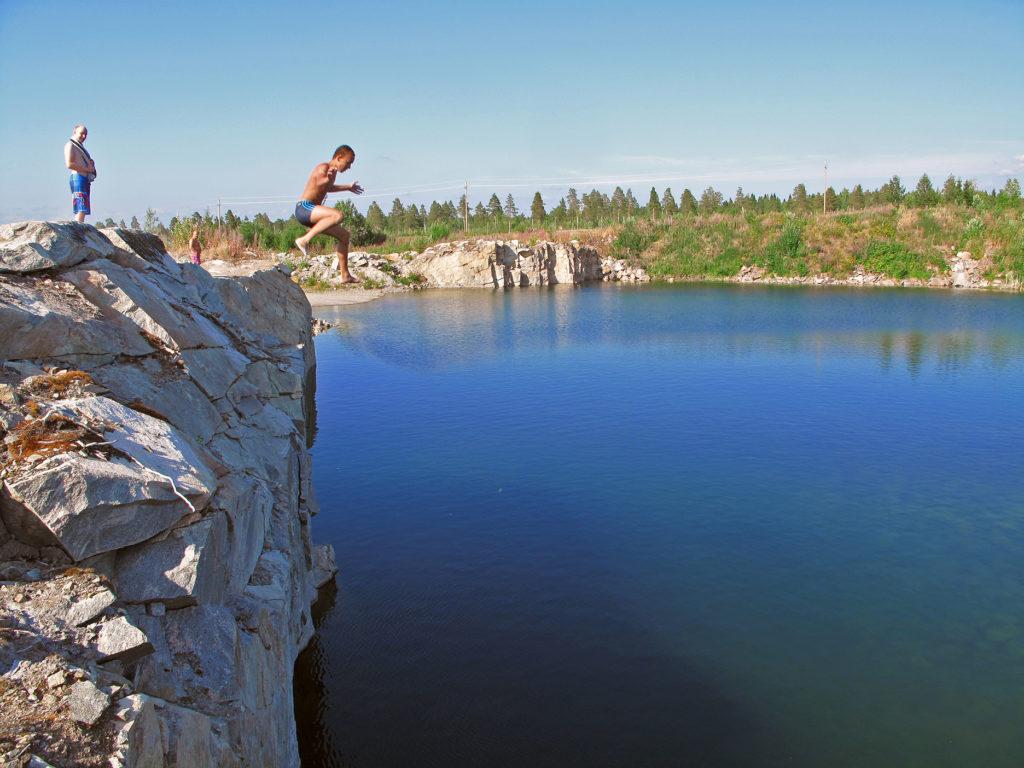 Mies hyppää korkealta louhitulta kalliolta veteen.