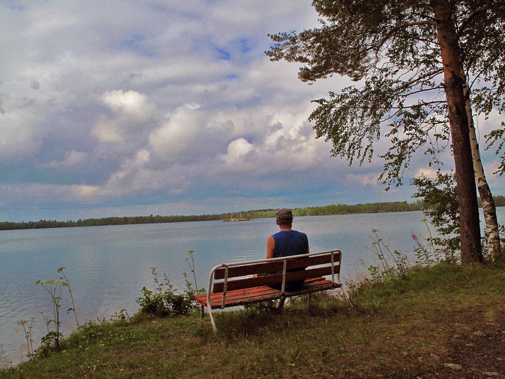 Mies istuu puistonpenkillä Veitsiluodon altaan reunalla.