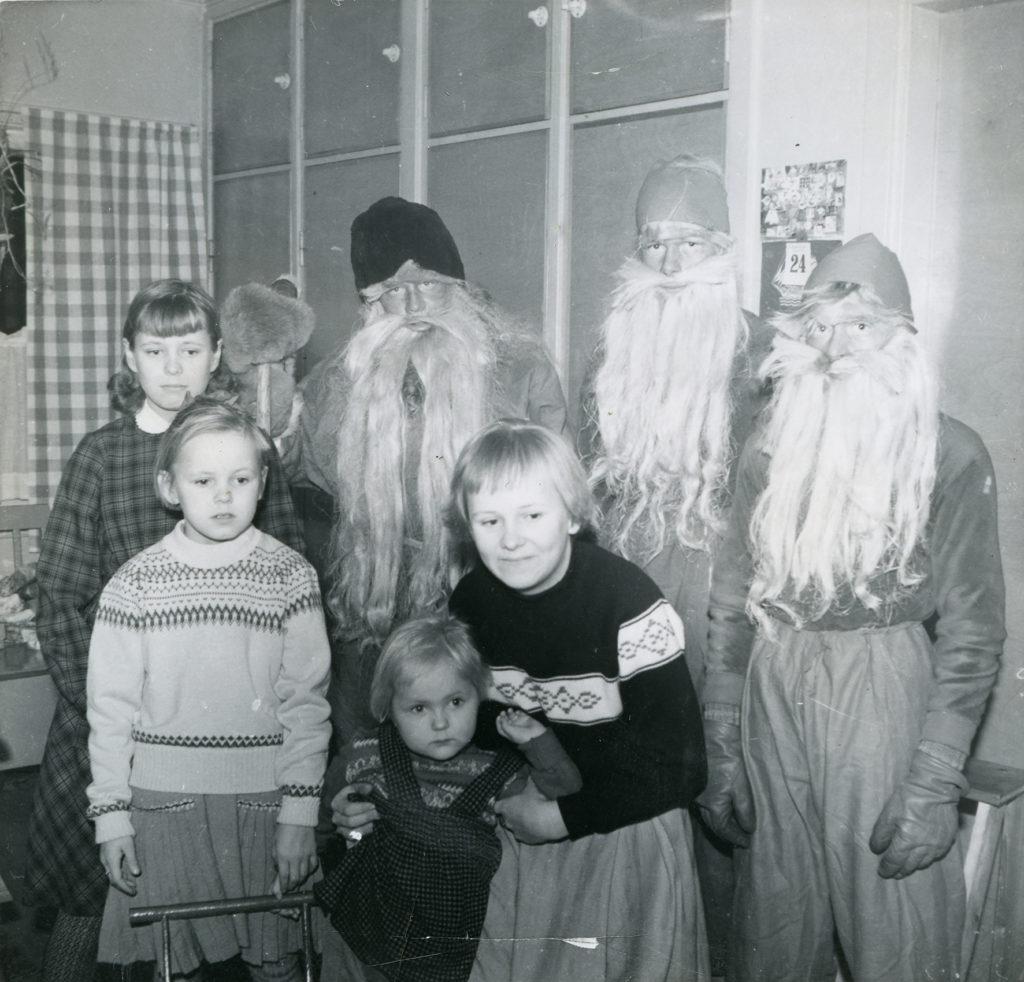 Joulupukki tonttuineen sekä lapsia