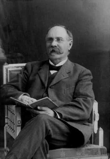 Mustavalkoinen kuva, jossa viiksekäs mies istuu tuolilla kirja kädessä