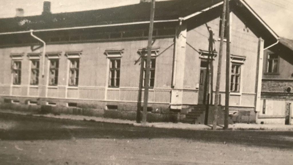 Mustavalkoinen kuva jossa vanha puinen asuinrakennus kadun risteyksessä