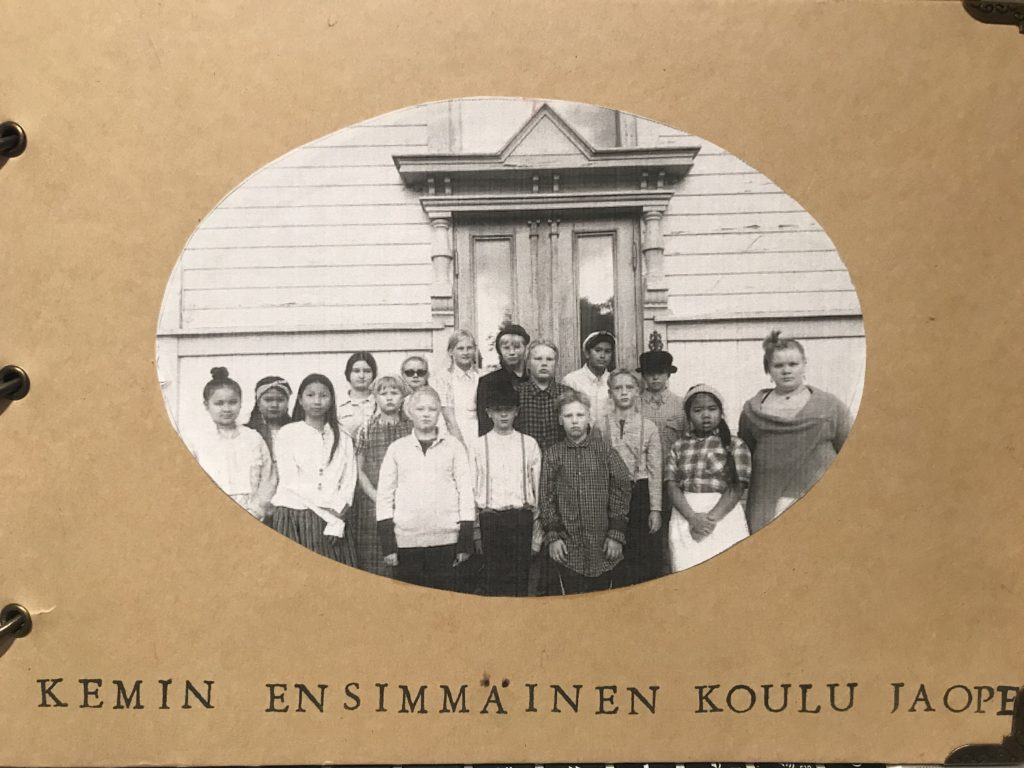 Kirjan kansi, jossa mustavalkoinen kuva Kemin ensimmäisen koulun oppilaista ja opettaja