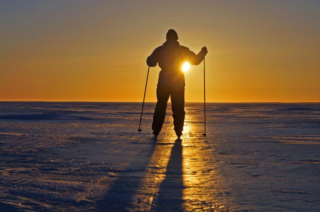 Mies hiihtää jäällä vasten auringonlaskua