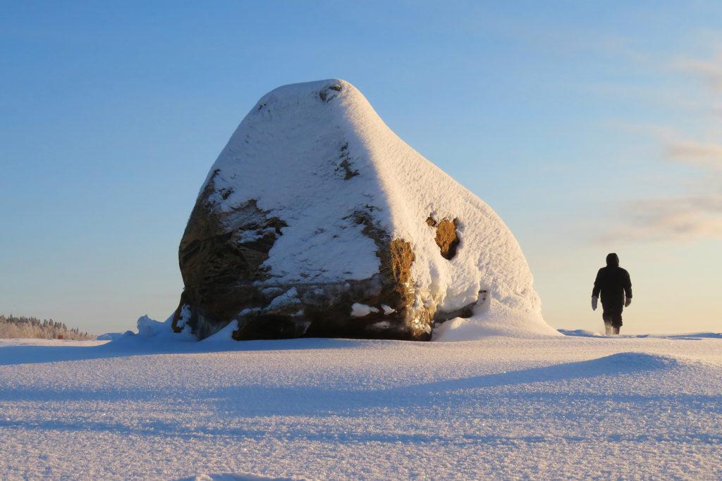 Mies kävelee hangella poispäin, vieressä jättimäinen lumen peitossa oleva kivi