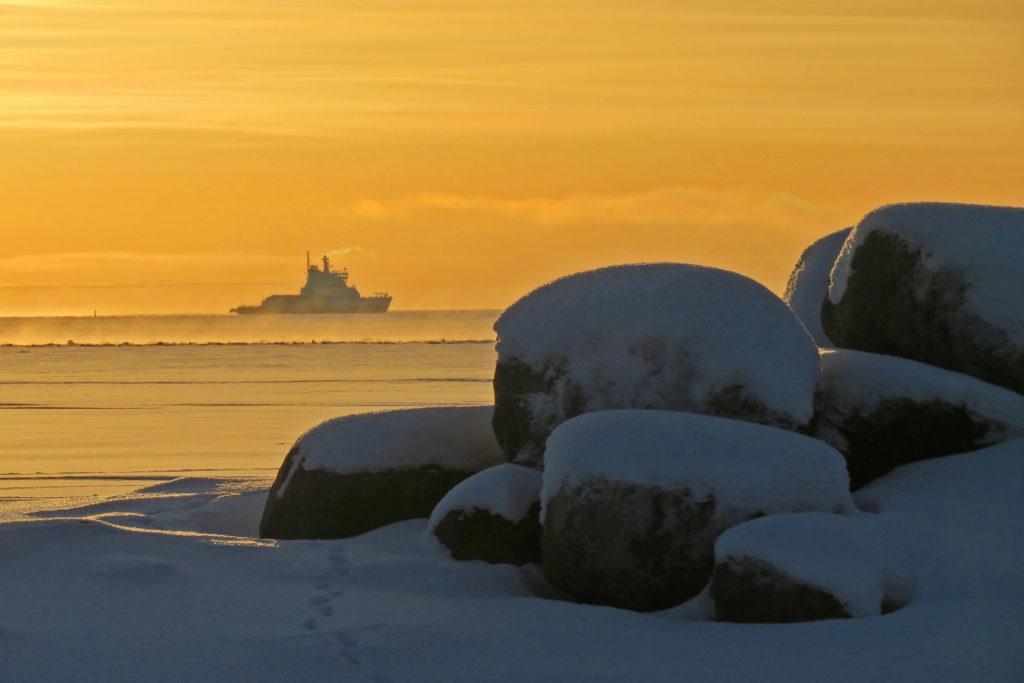Isoja kiviä etualalla, taustalla laiva hyisellä merellä