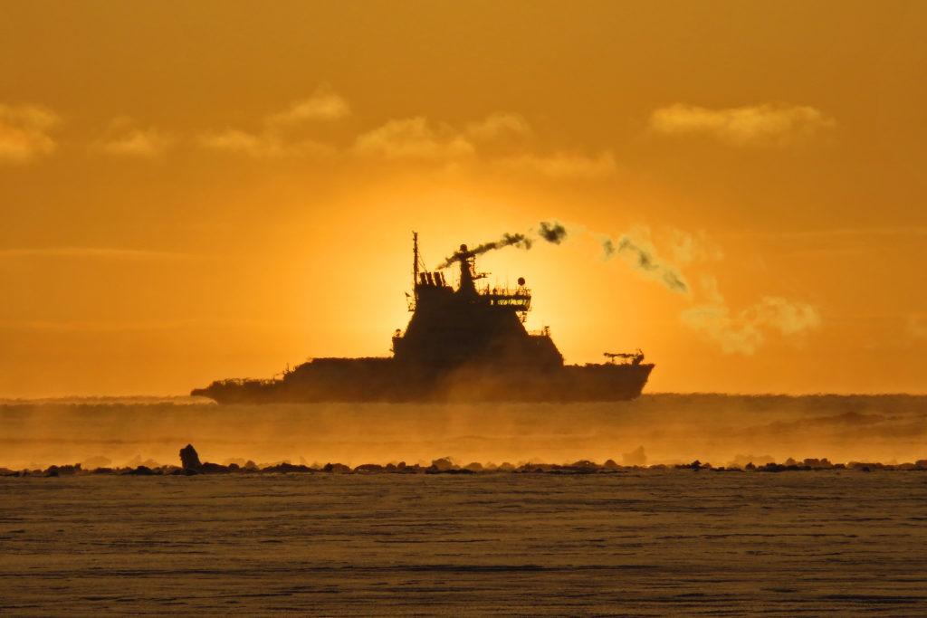 Laiva hyisellä merellä, aurinko värjää taivaan keltaiseksi
