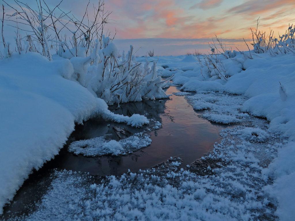 Luminen maisema, puro, jossa keskellä sulaa ja reunalla jääriitettä