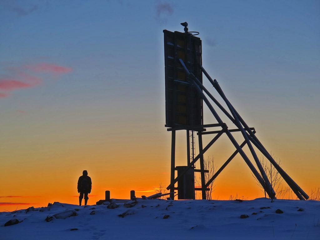 Mies seisoo selin linjamerkin vieressä, lumi peittää kivisen maiseman