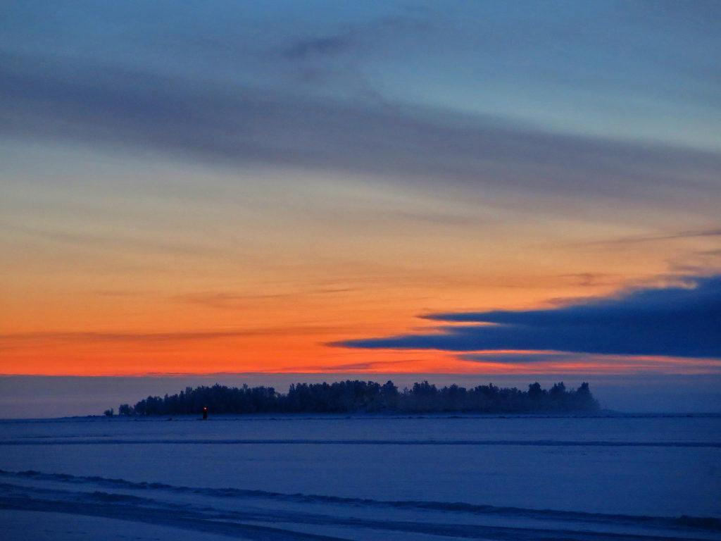 Talvinen kuva, lumi näyttää siniseltä, aurinko punertaa taivasta