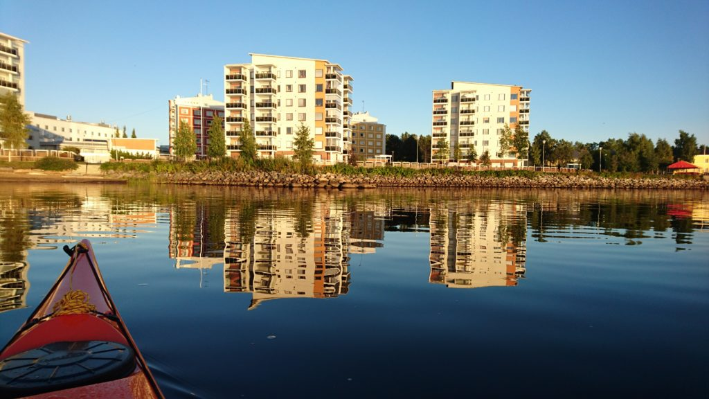 Meloja saapuu Kemin kaupunkiin kauniina kesäpäivänä. Meri on tyyni ja rannan kerrostalojen kuvajaiset näkyvät veden pinnassa.