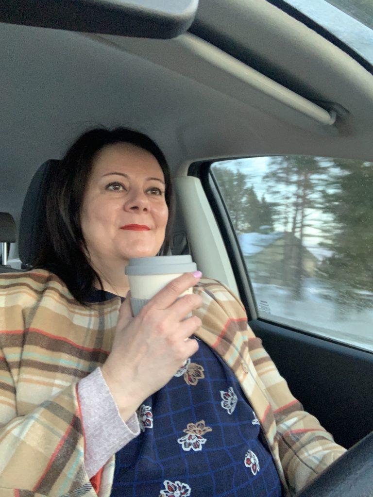 Nainen ajaa autoa, vaihtuva maisema näkyy auton ikkunasta