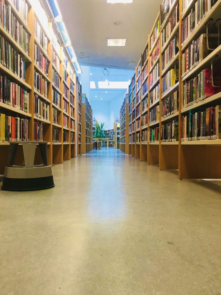Kirjaston käytävä kirjahyllyjen keskellä