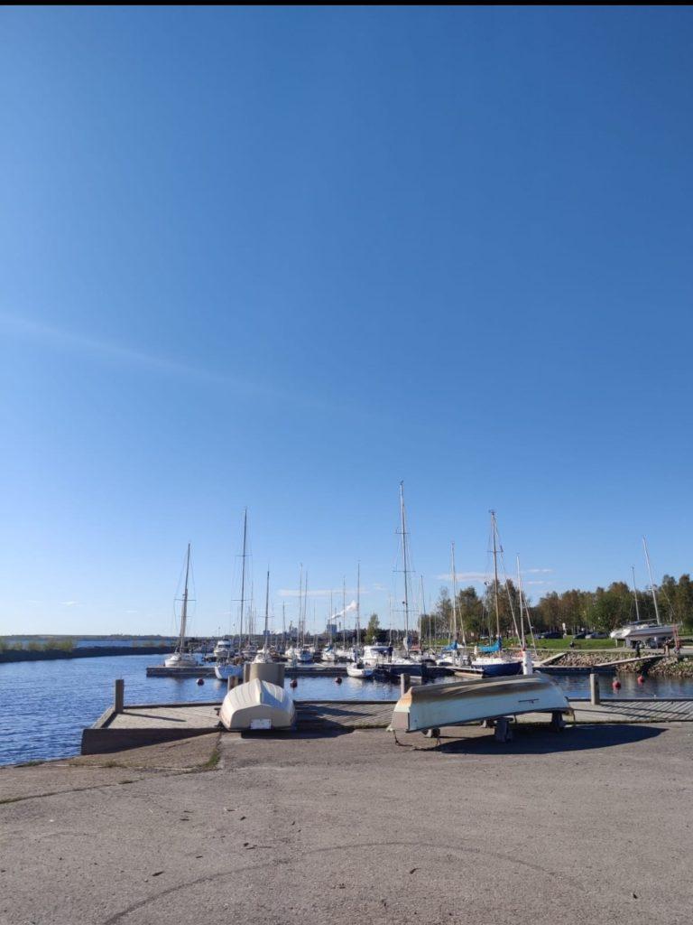 Etualalla kaksi venettä alaspäin asfaltilla, taustalla purjeveneitä laiturissa