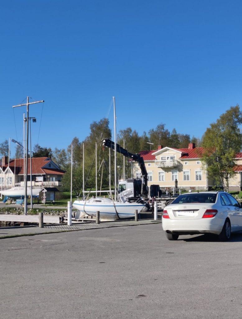 Valkoisen purjeveneen laskua vesille