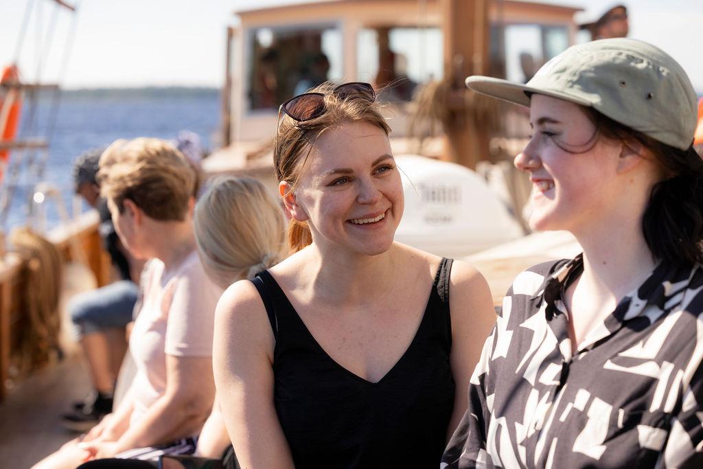 Korkeakouluharjoittelijat Johanna ja Ella istuvat Jähdin kannella ja nauttivat kauniista kesäsäästä ja meriristeilystä Jähdillä.